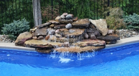 Freeform-pool-natural-waterfall-water-feature-cantiliever-coping-washed-tumbled-stone