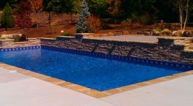 Stone-coping-stacked-stone-raised-wall-water-feature-2-tier-deck-broom-finish-concrete