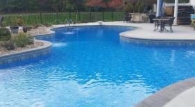 Freeform-large-water-feature-deck-jet-aluminum-fence-washed-tumbled-stone-landscaping